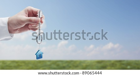Hand holding key with a keychain in the shape of the house. House key on background of nature