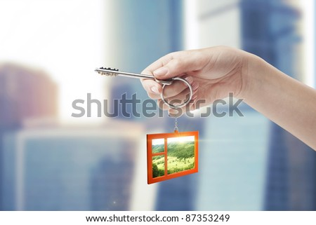 Hand holding key with a keychain in the shape of the window. Beautiful view behind a window of a green field with a blue sky. House key