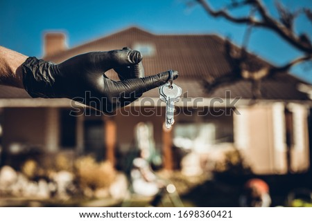 Hand holding keys, house in the background. Key holding in their hands in the street. Stay home and debt or financial obligation probelm with house. Covid-19 ncov or coronavirus quarantine concept.