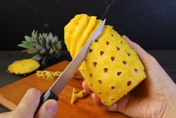 Hand holding knife for peeling and removing the hard and prickly eyes of a fresh ripe pineapple