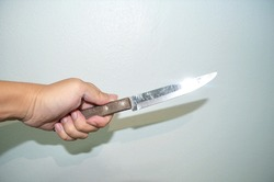 hand holding knife.kitchen knife in man hand.hand holding knife with white concrete background.killer with knife.