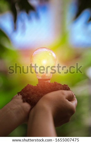 hand holding light bulb against nature, icons energy sources for renewable,