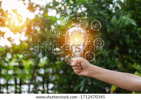 hand holding light bulb against nature, icons energy sources for renewable, Foto stock ©