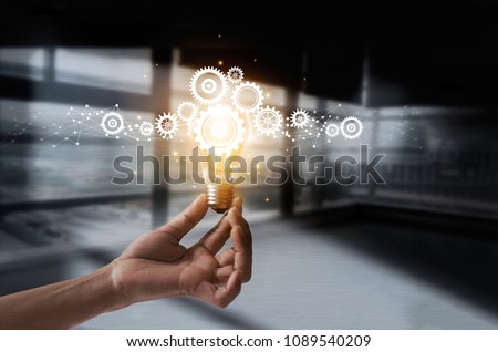 Hand holding light bulb and cog inside. Idea and imagination. Creative and inspiration. Innovation gears icon with network connection on metal texture background. Innovative technology in science
