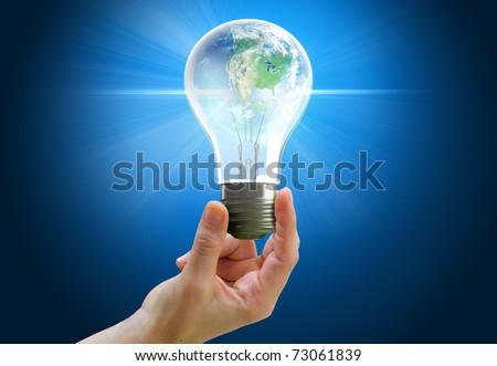 Hand holding light bulb globe symbolizing environmental care or green energy