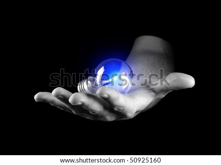 Hand holding light bulb isolated on black - stock photo