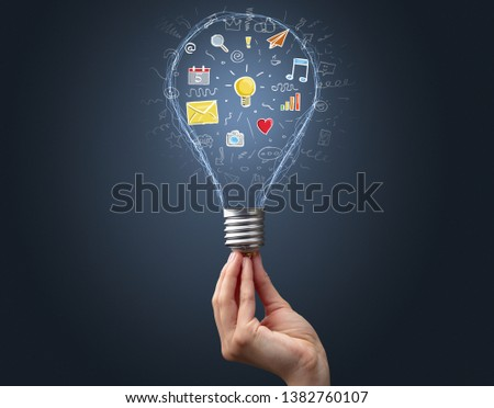 Hand holding light bulb on dark background. New apps concept #1382760107