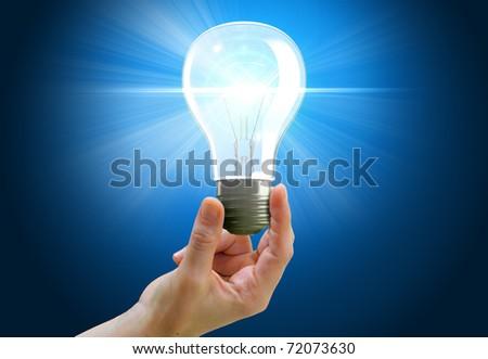 Hand holding light bulb symbolizing help, idea or inspiration