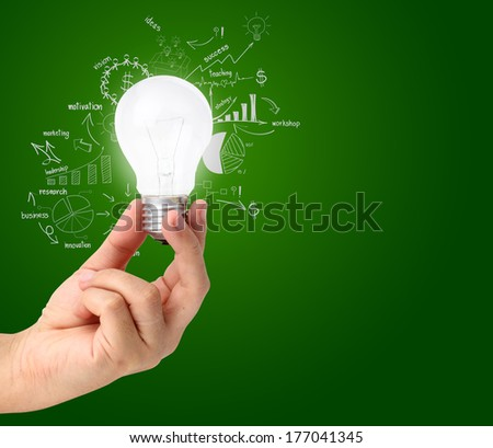 Hand holding light bulb with drawing charts and graphs business success strategy plan idea, Inspiration concept modern design - stock photo