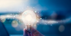 Hand holding light bulb with media icon on digital innovation and creativity are keys to success. Concept knowledge leads to ideas and inspiration.