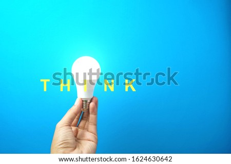 Hand holding light bulb with wording THINK on blue background, Creative conceptual image.