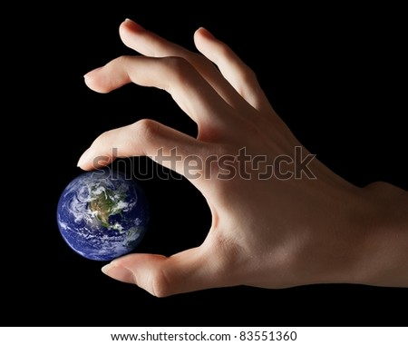 Hand holding little Earth as a symbol of power or responsibility. Earth globe image provided by NASA.