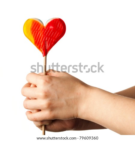 hand holding lollipop heart isolated on white