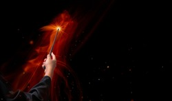 Hand holding Magic wand in the flames, Miracle magical stick Wizard tool on hot fire.