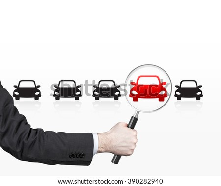 Hand holding magnifier over red picture of car in row of black cars. Front view. White background. Concept of choice.
