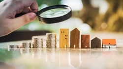 Hand holding magnifying glass and looking at house model with row of coin money, house selection, real estate concept.