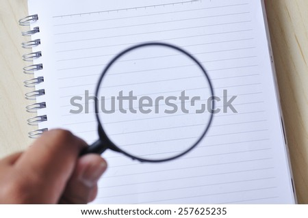 Hand Holding Magnifying Glass on Note Book, Focus on Note Book