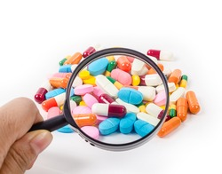 Hand holding magnifying glass with medicine pills on white background.