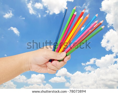 Hand holding many color pencils with blue sky