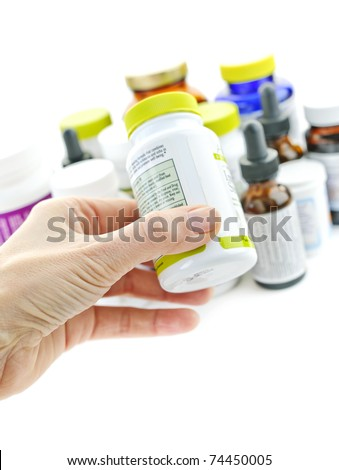 Hand holding medicine bottle to read label