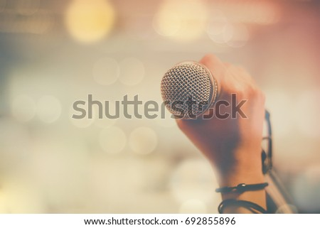 hand holding microphone and bokeh background, concept as music instrument in studio room and meeting hall #692855896