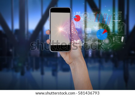Hand holding mobile phone against white background against room with large window looking on city