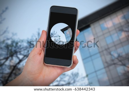 Hand holding mobile phone against white background against trees and building against clear sky #638442343