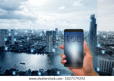 Hand holding mobile phone on blue tone smart city with wifi network connections background, communication network technology concept #1027179292