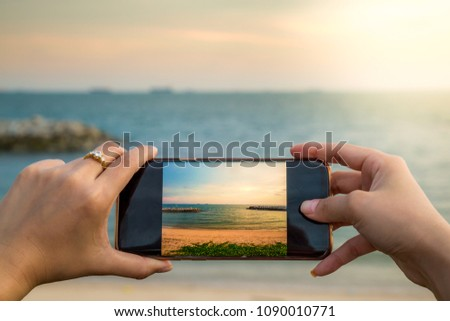 Hand holding mobile phone take photo of sea beach landscape with sunset sea background