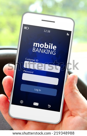 hand holding mobile phone with banking log in page in the car