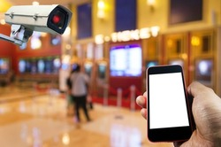 hand holding mobile phone with blank screen and CCTV, security indoor camera system operating at movie theater, internet, surveillance security and safety technology concept