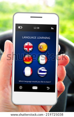 hand holding mobile phone with language learning application in the car