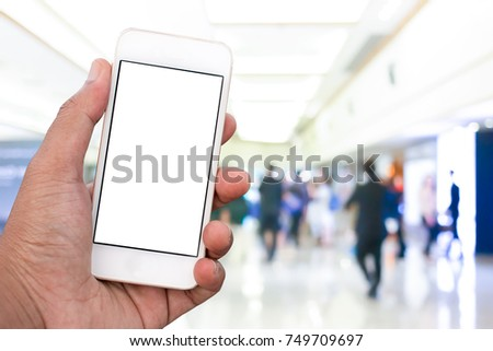 Hand holding mobile smart phone with blank screen in vertical position, blurred background - mockup template