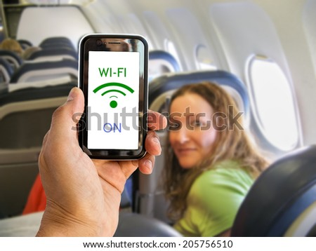 Hand holding mobile smart phone with connect wifi on the airplane