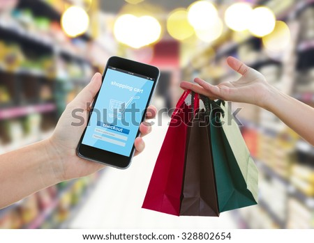 hand holding mobile smart phone with cyber mobile shop  on super market blur background and shopping bags - e-commerce and cyber  retail  marketing concept