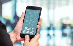 Hand holding mobile with Mobile banking word and features icon with blur office counter background,Digital Lifestyle concept.