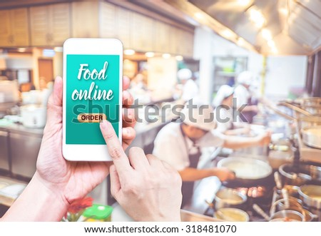 Hand holding mobile with Order food online with blur restaurant background, food online business concept.Leave space for adding your text