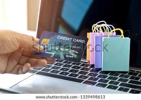 Hand holding mock up of credit card and colorful paper shopping bags on laptop keyboard. Consumer can buy products directly anywhere anytime from seller. Online shopping and e-commerce concept.