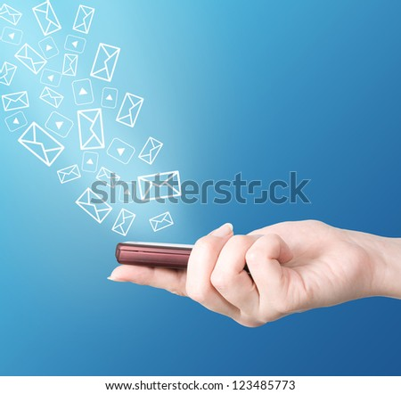 Hand holding modern mobile phone, video and letter symbols flaying away. Social media concept