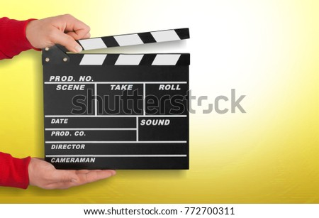 Hand holding movie clapper on yellow background #772700311