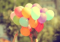 Hand holding multicolored balloons