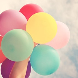 Hand holding multicolored balloons with retro instagram filter effect, summer or holiday concept