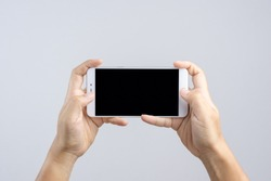 Hand holding new 6 inch smart phone with blank screen and  playing game gesture finger on white background