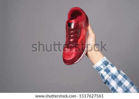 Hand holding new red sport sneaker isolated on gray background.