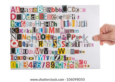 Hand holding newspaper clippings alphabet with letters, numbers and symbols, isolated on white background.