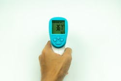 Hand holding non-contact infrared thermometer isolated on white background to measure a body temperature.