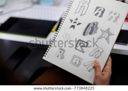 Photo of  Hand Holding Notebook With Drew Brand Logo Creative Design Ideas