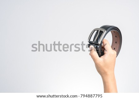 Hand holding old style or retro black leather belt with metal head on white background