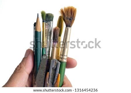 Hand holding Old used paintbrushes.Used dirty paint brushes on white background