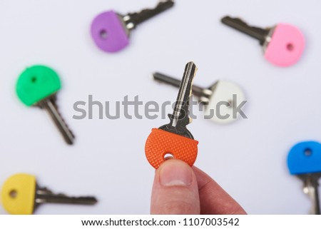 Hand holding one colorful key from lock on blured background